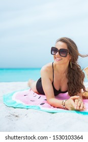 happy modern 40 year old woman with long curly hair in elegant black swimsuit on a white beach sun bathing while laying on a round towel and looking into the distance.