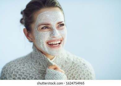 happy modern 40 years old woman in roll neck sweater and cardigan with white facial mask as part of winter skin care looking at copy space on winter light blue background.