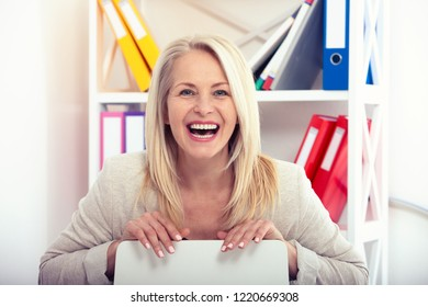 Happy modern businesswoman. Beautiful middle aged woman looking at camera with smile while siting in the office. Female face close-up