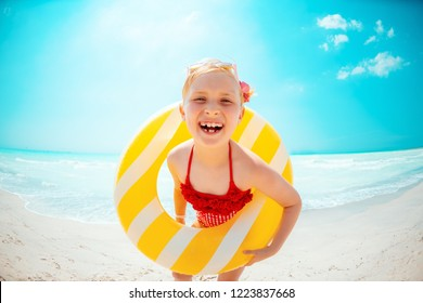 happy modern child in red swimsuit with yellow inflatable lifebuoy on the beach