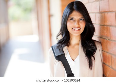 6b637a15fe happy modern college girl on campus. Smiling indian woman with arms crossed  against white background