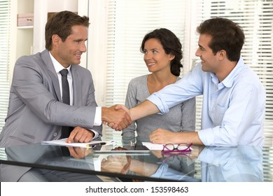 Happy modern couple seal a deal with their personal financial advisor , handshake , at home