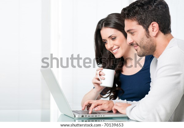 Happy modern couple surfing the net and working on laptop at home