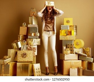happy modern fashion-monger in gold beige clothes playing with gift box among 2 piles of golden gifts in front of a plain wall. first minute shopping with huge gift opportunities concept. or birthday