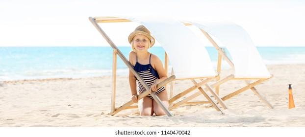 happy modern girl in swimsuit on the beach hiding under beach chair