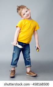 Happy modern kid playing with toy airplane and car. He  wearing a yellow t-shirt and jeans. Studio shot