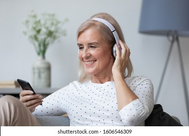 Happy modern mature female retiree grandmother wear earphones relax on couch listen to music on smartphone, smiling senior woman rest enjoy high quality sound use headphones and cellphone