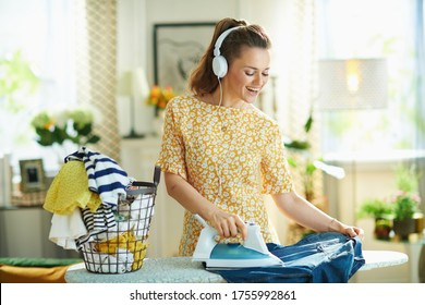 happy modern middle age woman in yellow dress with washed clothes basket ironing on ironing board while listening to the music with headphones in the modern house in sunny day.