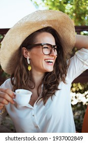 happy modern middle aged woman in white shirt with cup of coffee, hat and eyeglasses in the terrace.