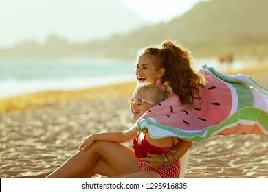 happy modern mother and child in beachwear holding watermelon towel sitting on the seashore in the evening having fun time. minimal to no crowd peace. blond hair child wearing sunglasses.