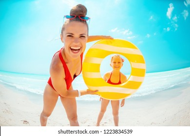 happy modern mother and child in red swimwear with yellow inflatable lifebuoy on the beach