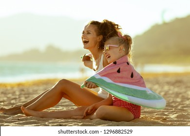 01a49ce614afd happy modern mother and child in swimwear on the seashore in the evening  having fun time