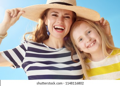 happy modern mother and daughter against blue sky