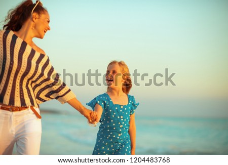 happy modern mother and daughter on the seashore at sunset walking