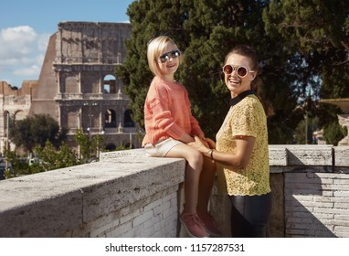 happy modern mother and daughter travellers not far from Colosseum sightseeing