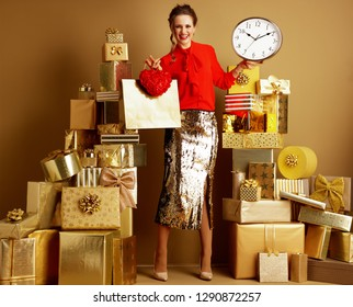 Happy modern shopper woman in red blouse and golden sparkly sequin pencil skirt with shopping bag and red heart showing clock among 2 piles of golden gifts in front of a plain wall. Valentine's Day.