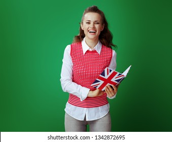 happy modern student woman in grey jeans and pink sleeveless shirt looking through records of English class in United Kingdom flag coloured notebook on chalkboard green background.