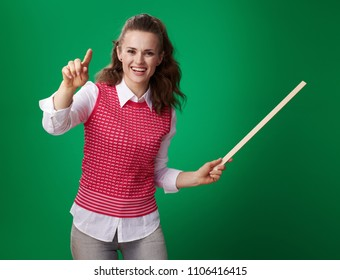 happy modern student woman in a red waistcoat with a pointer pointing in camera isolated on green