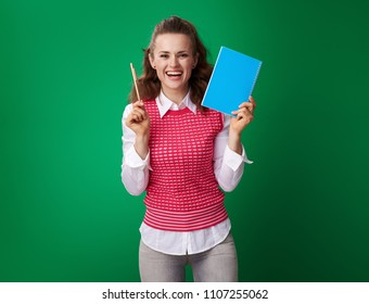 happy modern student woman in a red waistcoat showing a blue notebook and a pen on green background