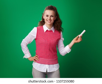 happy modern student woman in a red waistcoat with a piece of chalk against green background