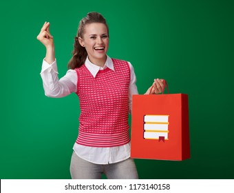 happy modern student woman in a red waistcoat with shopping bag with books fingers snapping against green background