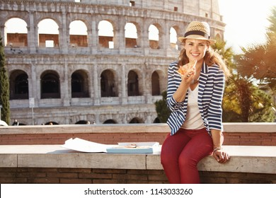 happy modern tourist woman in a striped jacket in Rome, Italy eating pizza