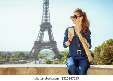 happy modern traveller woman in blue jeans overall with coffee cup and baguette in Paris, France.