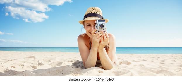 happy modern woman in beachwear taking photo with retro photo camera on the seacoast