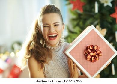 happy modern woman with Christmas present box near Christmas tree