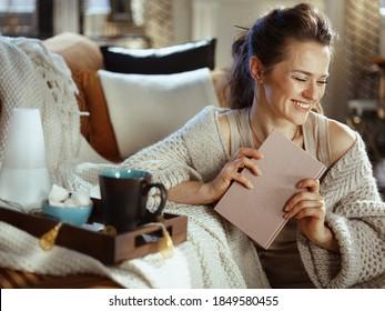 Happy moderne Frau aus gewirktem gemütlichem Cardigan mit Buch, Tray, Aromalampe, Tasse und Gebäck im modernen Wohnzimmer an sonnigen Herbsttag.