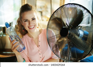 happy modern woman in the modern living room in sunny hot summer day showing cold bottle of water and enjoying fresh air in the front of working fan.