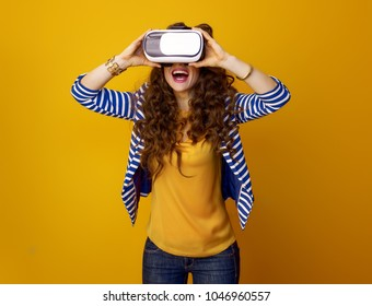 happy modern woman with long wavy brunette hair against yellow background using VR gear