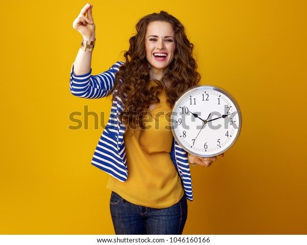 happy modern woman with long wavy brunette hair on yellow background with clock snapping fingers
