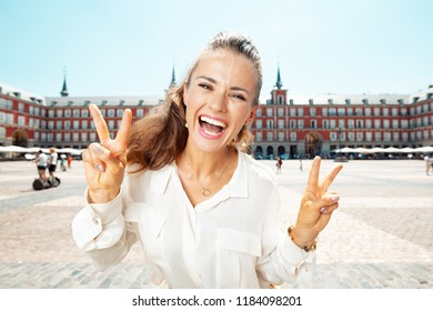 happy modern woman at Plaza Mayor showing victory gesture