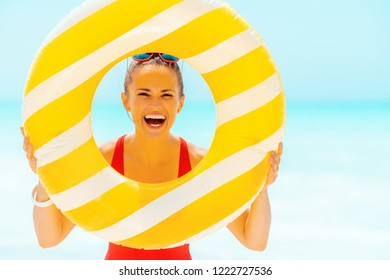 happy modern woman in red beachwear on the seacoast looking through yellow inflatable lifebuoy