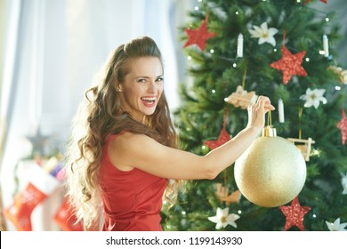 happy modern woman in red dress near Christmas tree hanging big gold Christmas ball on Christmas tree