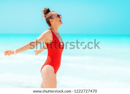 happy modern woman in red swimsuit on the beach rejoicing