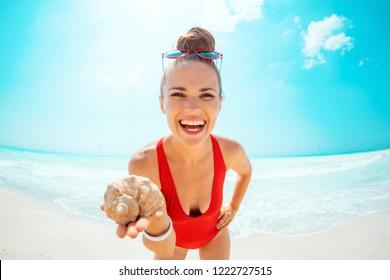 happy modern woman in red swimwear on the beach showing a sea shell