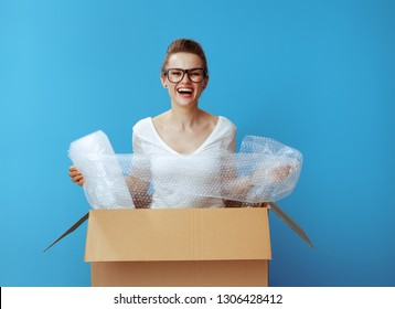 happy modern woman in white t-shirt in a cardboard box with air bubble film packaging material against blue background