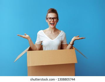 happy modern woman in white t-shirt presenting something on empty palm pops out of a cardboard box and against blue background