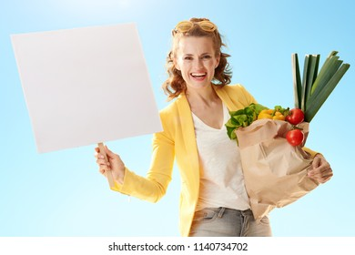 happy modern woman in yellow jacket with paper bag with groceries showing blank poster against blue sky