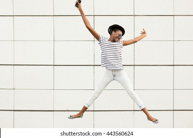 happy modern young black woman with sunglasses, hat and striped shirt  listening music outside and jumping