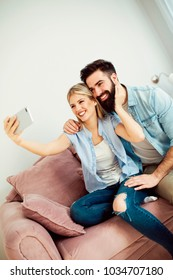Happy modern young couple taking photo with mobile device