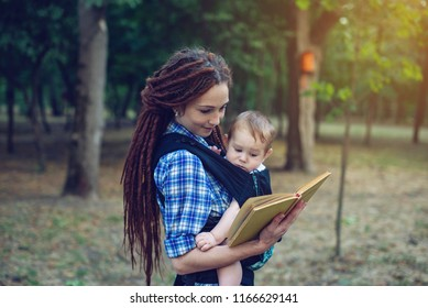 Happy mom with a baby in a sling reading a book in the Park. The concept of children's education in family life