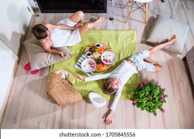 Happy mom and boy imitating summer picnic time on green grass blanket near TV screen. Travelling with family. Coronavirus situation in tourism industry. Quarantine. Stay at home. Isolation. Top view