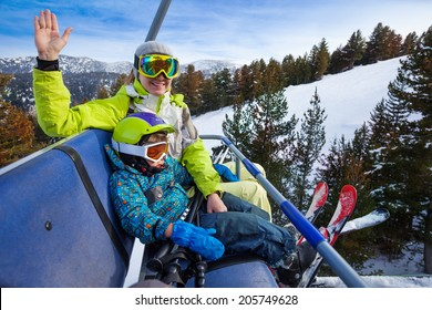 Happy mom and boy in ski masks seat on elevator