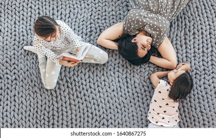 Happy mom with children in sleepwear lying down and relaxing with a book on chunky giant woolen blanket, top view