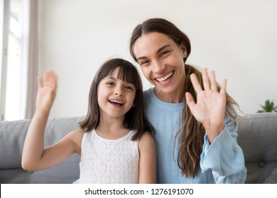 Happy mom and cute kid daughter waving hands looking at camera, portrait of friendly mother or baby sitter and child girl smiling talking at webcam saying hello hi or goodbye making online call vlog