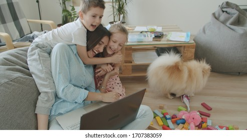 Happy mom and cute kids having fun talking using laptop at home, smiling mother teach little children online shopping. Young woman works from home. Self-isolation