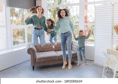 Happy mom with cute little baby son daughter holding hands jumping in living room, carefree parents and little kids having fun flying in the air laughing dancing together at home